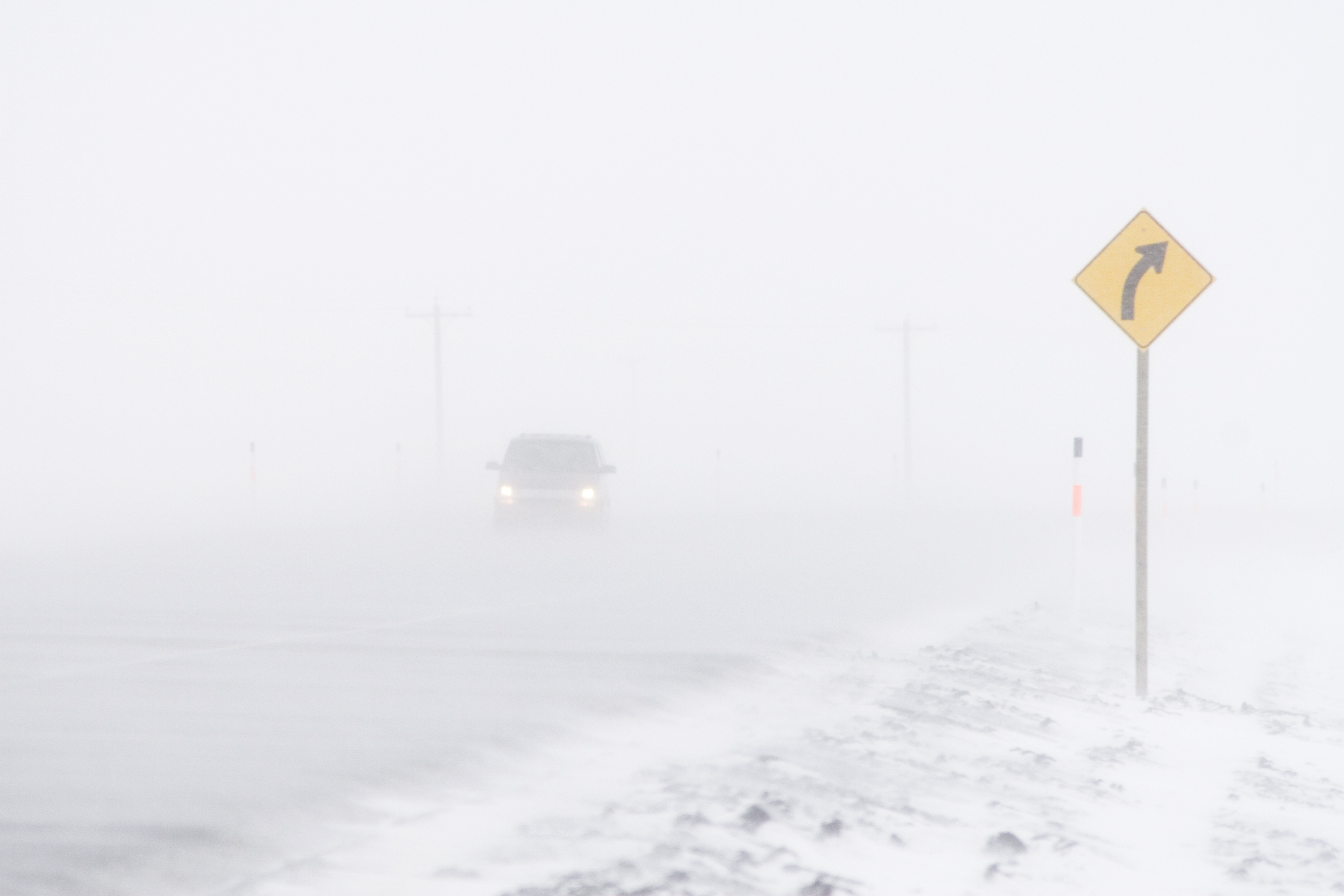 A car travels down the highway in a blizzard.
